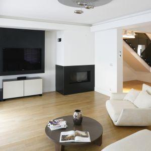 Prosta, biała szafka pod telewizor doskonale pasuje do ściany wykończonej biały i czarnym kolorem. Projekt: Kamila Paszkowska. Fot. Bartosz Jarosz