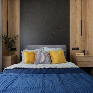 Ściana za łóżkiem w sypialni - w tym projekcie zastosowano ciekawy pomysł z drewnianą zabudową i ciemnymi płytami wielkoformatowymi z rysunkiem kamienia. Projekt: pracownia M-Studio. Fot. Radek Słowik
