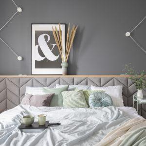 Ściana za łóżkiem w sypialni wykończono szarą farbą i udekorowana plakatem. Uwagę zwraca tapicerowany wysoki zagłówek łóżka. Projekt: Zu Projektuje. Fot. Pion Poziom