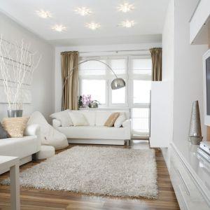 Jasny salon, urządzony w bieli. Aranżację świetnie dopełnia drewno i srebrne elementy. Projekt: Małgorzata Mazur. Fot. Bartosz Jarosz