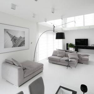 W tym salonie króluje biel. W tym kolorze są zarówno ściany, jak i podłoga. Projekt Ewelina Pik, Maria Biegańska. Fot. Bartosz Jarosz