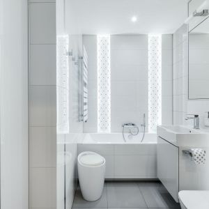 Ściany w łazience wykończono białymi, błyszczącymi płytkami. Charakter wnętrzu dodaje dekoracyjna ściana za wanną z podświetloną mozaiką Tubądzin Abisso White. Projekt: Justyna Mojżyk, poliFORMA. Fot. Monika Filipiuk-Obałek