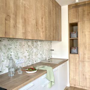 Między kuchennymi szafkami ścianę wykończono tapetą. Projekt: Zuzanna Kuc, pracownia ZU Projektuje