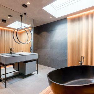 Ściany w łazience wykończono drewnem teakowym, wykorzystywanym na jachtach oraz antracytowym, wielkoformatowym gresem. Projekt: Anna i Krzysztof Paszkowscy-Thurow. Fot. Bartłomiej Bieliński