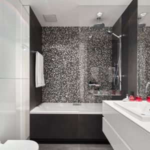 Ściany w łazience wykończono płytki w biało-czarnej kolorystyce. Bardzo ciekawie prezentuje się ściana za wanną, którą zdobi piękna mozaika. Projekt: Bibianna Stein-Ostaszewska (Bibi Space). Fot. Olo Studio