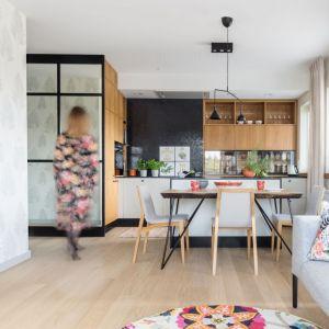 Kuchnia otwarta na salon. Od pokoju kuchnię oddziela półwysep i dodatkowo stół z krzesłami. Projekt: Agnieszka Morawiec, Pracownia Projektowa Siedem. Fot. Pion Poziom