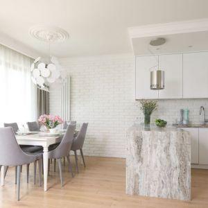 Kuchnia otwarta na salon.  Kuchnia w kształcie litery L, białe fronty, wyspa kuchenna z rysunkiem kamienia. Projekt: Laura Sulzik. Fot. Bartosz Jarosz