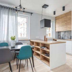 Kuchnia otwarta na salon. Kuchnię od jadalni i salonu oddziela duża wyspa kuchenna z praktycznymi półkami. Projekt: Deer Design