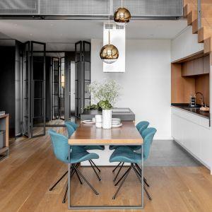 Dwie lampy wiszące o prostej, ładnej formie doskonale pasują do nowoczesnej, otwartej strefy dziennej. Projekt: JMW Architekci. Fot. Ola Dermont i JMW Architekci