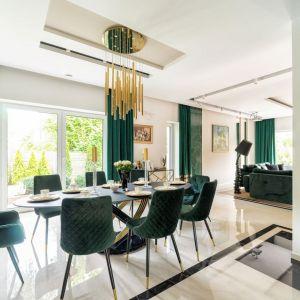 Złote oświetlenie nad stołem nadało jadalni elegancki charakter. Projekt Trędowska Design. Fot Michał Bachulski