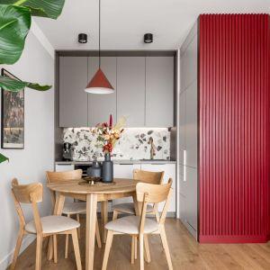 Czerwona lampa nad stołem w jadalni wygląda super. Projekt: Maria Nielubszyc, pracownia PURA design. Fot.  Jakub Nanowski