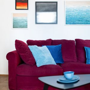 W salonie wyeksponowano obrazy właściciela mieszkania. Projekt: Maria Nielubszyc, pracownia Pura Design. Fot. Jakub Nanowski