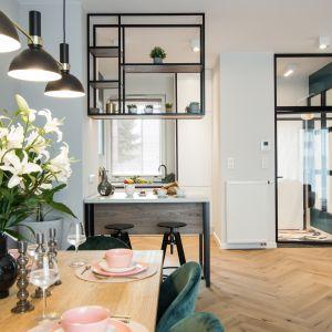 Przeszklone drzwi z czarnymi ramkami prowadzą z holu do otwartego salonu z kuchnią. Projekt: Kodo Projektowanie i Realizacja Wnętrz