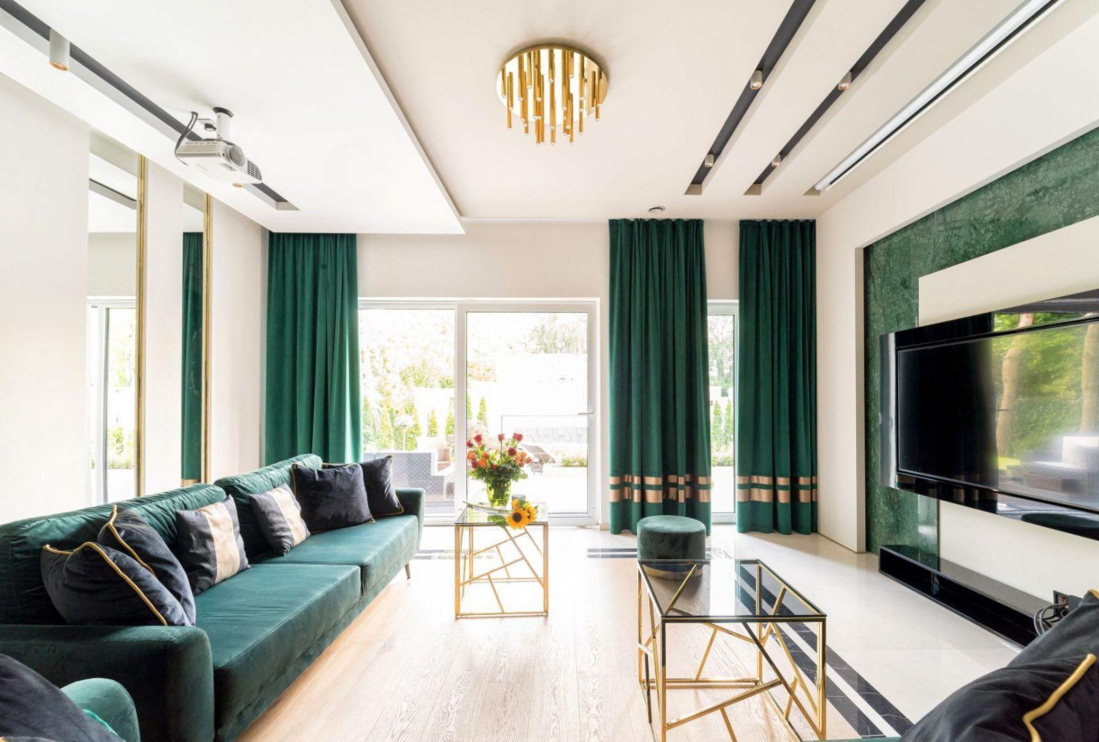 Okno w eleganckim salonie zdobią ciemne, zielony zasłony idealnie pasujące do sofy w takim samym kolorze. Projekt Trędowska Design. Fot Michał Bachulski