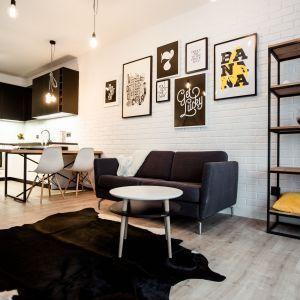 Mały salon z czarno-białą kuchnią. Projekt Nowa Papiernia fot. Anna Kopeć