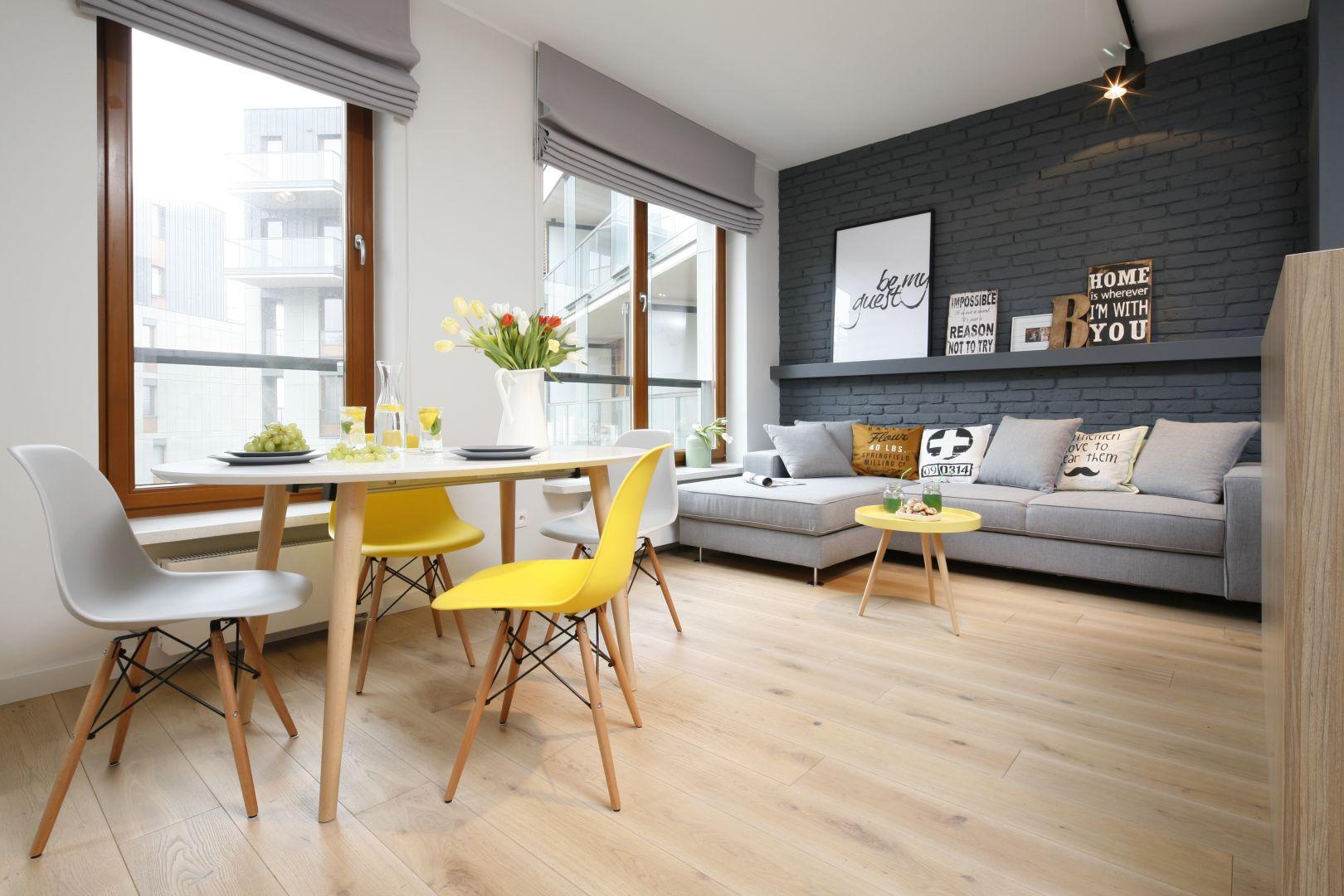 Mała jadalnia znajduje się przy dużym oknie. Kolorowe krzesła wyglądają super. Projekt Ola Kołodziej, Ula Szmyt