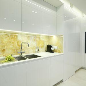 Ścianę nad blatem zabezpiecza onyks, pięknie podświetlony. Projekt Anna Fodemska. Fot. Bartosz Jarosz