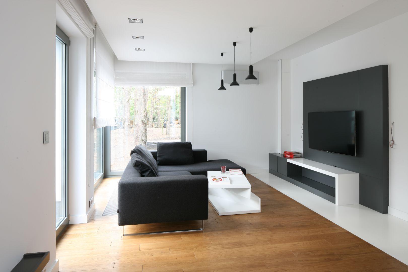 Czarna ściana za telewizorem i kanapa świetnie wyglądają w połączeniu z białym ścianami i drewnianą podłogą. Projekt: Katarzyna Kiełek, Agnieszka Komorowska-Różycka. Fot. Bartosz Jarosz