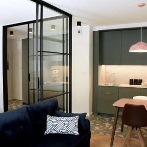 W tej kawalerce sypialnia została oddzielona od kuchni i pokoju szklaną ścianką z czarnymi ramkami. Fot. Raumplus