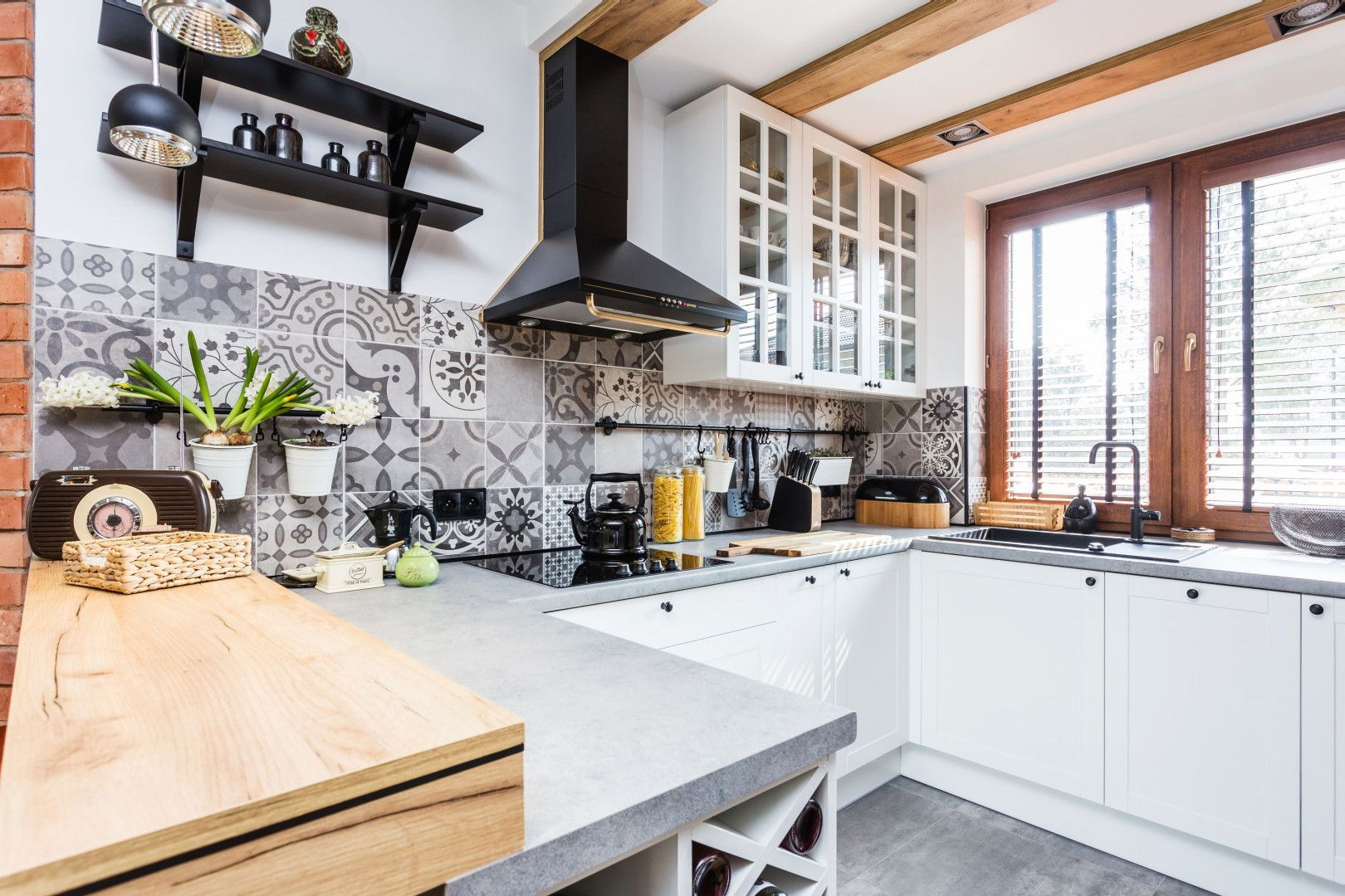 Piękna biała kuchnia w klasycznym stylu. Nad blatem płytki patchworkowe. Projekt: Agnieszka Hincz. Fot. Michał Młynarczyk