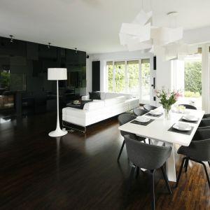 Czarna zabudowa meblowa w salonie idealnie pasuje do białej kanapy i ciemnej, drewnianej podłogi. Projekt: Justyna Smolec. Fot. Bartosz Jarosz