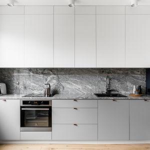 Wzorzysty kamień granit Viscont White pojawił się na blacie i plecach kuchni. Autorzy projektu: Raca Architekci. Zdjęcia: foto&mohito