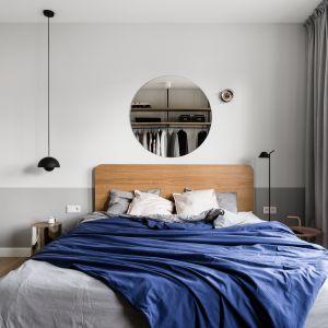 W sypialni stoi proste łóżko na metalowych nogach z wysokim drewnianym zagłówkiem. Oświetlenie to model Flower Pot marki &Tradition. Autorzy projektu: Raca Architekci. Zdjęcia: foto&mohito