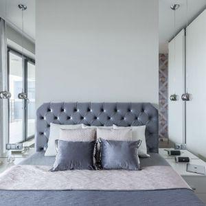 Po obu stronach tapicerowanego łóżka znajdują się lustra, które optycznie powiększają i rozświetlają przestrzeń sypialni. Projekt: Justyna Mojżyk, poliFORMA. Fot. Monika Filipiuk-Obałek