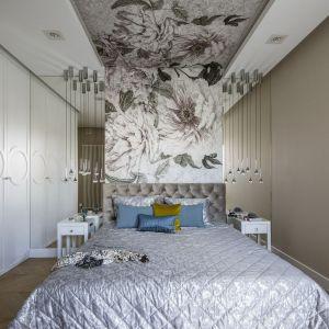 Ścianę za łóżkiem pięknie zdobi florystyczna tapeta biegnąca przez ścianę oraz całą długość sufitu. Projekt Tissu Architecture. Fot. Yassen Hristov