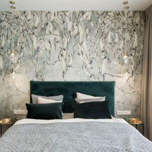 Ścianę za łóżkiem wykończono oryginalną tapetą z naturalnym motywem, prowadząca dialog z zielenią ścian i dyskretnym oświetleniem w stylu vintage. Projekt i wykonanie: KODO Projekty i Realizacje Wnętrz