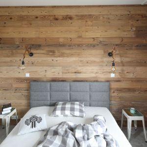 Ścianę za łóżkiem wykończono drewnem. Projekt: Agnieszka Żyła. Fot. Bartosz Jarosz