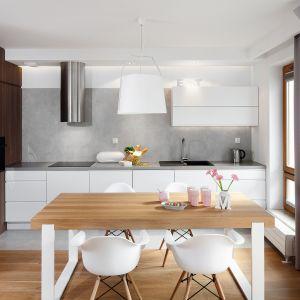 Biała kuchnia w prostym stylu. Ociepla ją drewniany blat stołu na białych nogach. Projekt: Przemysław Kuśmierek. Fot. Bartosz Jarosz