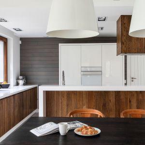 Nowoczesna aranżacja białej kuchni ocieplonej eleganckim ciemnym drewnem. Projekt: MAFGROUP