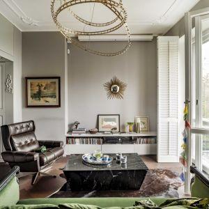 W sercu salonu znalazła się XIX-wieczna sofa obita współczesną tkaniną w kolorze ciemnej zieleni. Tworzy zgrany duet z wykonanym na zamówienie stolikiem z marmuru. Fot. Rafał Lipski. Stylizacja: Barbara Dereń-Marzec