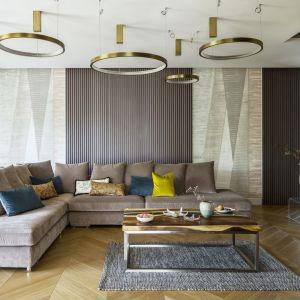 W eleganckim salonie króluje rozłożysta, jasna kanapa z kolorowymi poduszkami. To one wprowadzają do wnętrza barwne akcenty, które świetnie wyglądają na tle neutralnej palety beży, brązów i czerni. Projekt: Tissu Architecture. Fot. Yassen Hristov