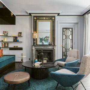 W elegancko urządzony salonie wzrok przyciąga kominek z lustrem w pięknej, czarno-złotej ramie nad paleniskiem. Projekt i zdjęcia: Gerard Faivre Paris