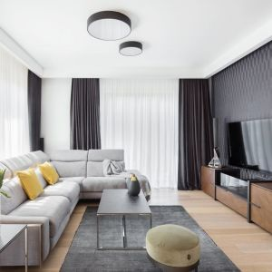 Ciemny szary dywan tworzy spójną, estetyczną całość z zasłonami oraz z nieco jaśniejszą kanapą. Projekt: Katarzyna Maciejewska. Fot. Dekorialove