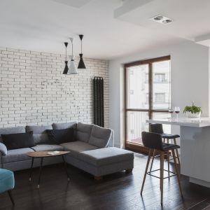 Salon i kuchnię urządzono nowocześnie. Zastosowanie jasnych kolorów sprawiło, że otwarte wnętrze wydaje się większe. Projekt i zdjęcia: MAFGROUP