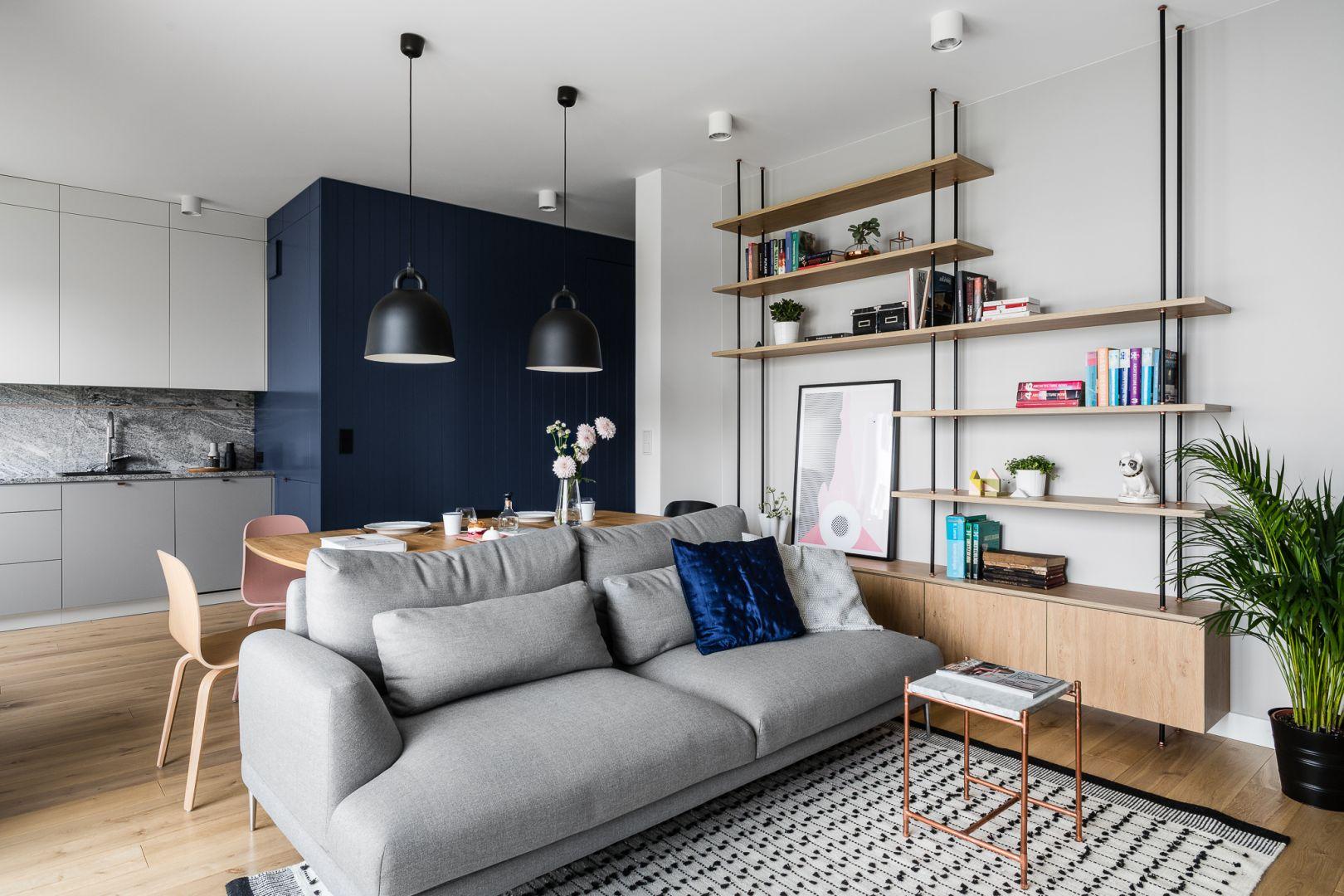 Jak łączyć ściany i podłogę w salonie. Jasne drewniane podłogi i jasne ściany to świetne tło dla granatowej ściany. Projekt:  Raca Architekci. Zdjęcia: Fotomohito
