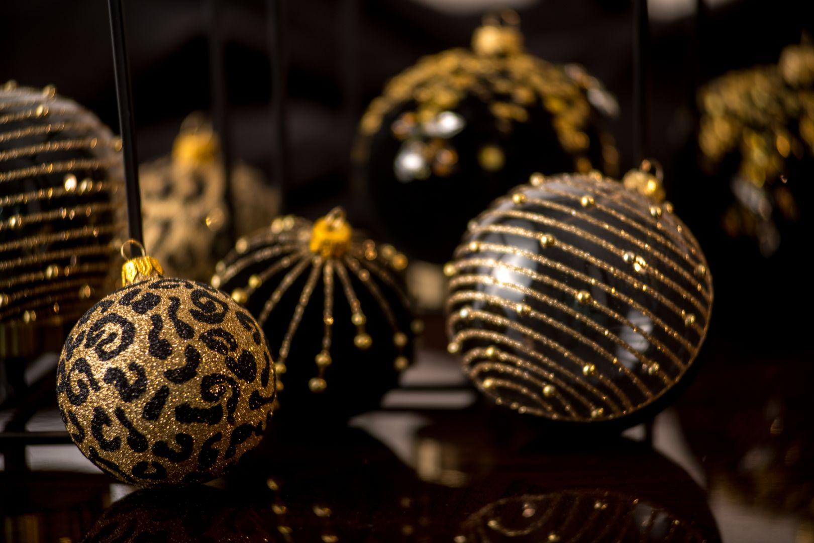 Bombki Line i Dot zmysłowo łączą czerń i złoto. Pierwsza w połowie pokryta jest czarnym flokiem, w drugiej połowie to czyste, transparentne szkło. Całość zdobi dekoracja ze złotego brokatu i złotych półpereł. Druga w całości pokryta czarnym flokiem, udekorowana jest w cienkie, subtelne linie wykonane złotym brokatem. Motywem dekoracyjnym tu także są złote półperły.  Fot. Kler