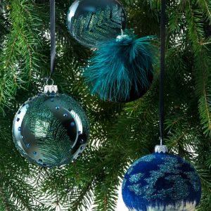 W kolekcji odnajdziemy okrągłą bombkę Diamond lakierowaną na turkusowy kolor. Zdobi ją motyw liści wykonanych brokatem i kryształkami. Tworzy ona piękny duet z bombką Brilliant w kolorze niebieskim (podkład pawiowy lakier), którą ozdobiono motywem liści wykonanych brokatem. Fot. Kler
