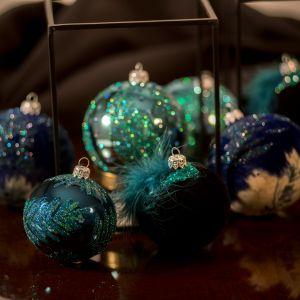 Kolekcję uzupełniają bombki Velvet i Pavo. Pierwsza to bombka okrągła pokryta od góry flokiem w kolorze ciemnego szafiru i brokatu, od dołu zaś ma podkład w kolorze ciemnego szafiru i beżu. W całości daje to ciekawy wizualnie efekt tak modnego w dekoracji wnętrz marmuru. Druga cała pokryta jest czarnym flokiem, a od góry ozdobiona kamykami w kolorze szmaragdu oraz piórem marabu. Dzięki naturalnym piórom prezentuje się ona niezwykle wytwornie i elegancko. Fot. Kler