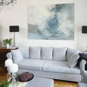 Salon urządzono elegancko i przytulnie. Wygodna sofa oraz fotele wyróżniają się pięknie zdobionymi podłokietnikami. Projekt: Iwona Kurkowska. Fot. Bartosz Jarosz