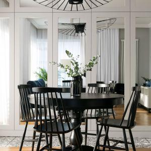w jadalni znalazł się stylowy czarny stół z drewna, drewniane krzesła-patyczaki i imponująca lampa, wszystko w eleganckiej czerni. Projekt: Paulina Zwolak, Jakub Nieć, pracownia Projektyw. Zdjęcia: Jakub Dziedzic