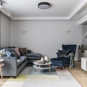 Wybierz szary, klasyczny kolor tapicerki sofy, który będzie wyglądał jeszcze bardziej stylowo, jeśli udekorujesz go poduszkami w geometryczne wzory. Projekt Magma. Fot. Fotomohito