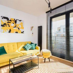 W małym salonie postawiono na kolory. Wzrok przyciąga kanapa oraz puf w intensywnym, słonecznym kolorze żółtym oraz abstrakcyjny obraz na ścianie. Projekt: Karolina Karwowska. Fot. Michał Młynarczyk