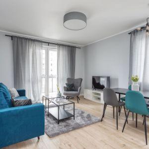 Szary salon pięknie ożywia kolor niebieski. Salon został połączony z jadalnią oraz kuchnią. Projekt i zdjęcia: Deer Design