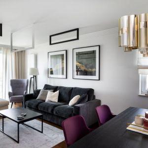 Jasne poduszki na ciemnej sofie wyglądają super. Projekt : Dekorian Home x Architaste. Fot. Dominika Wilk