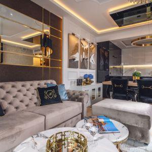 Czarne poduszki ze złotym wzorem to świetny wybór do salonu urządzanego w stylu glamour. Jest jasne, eleganckie i bardzo przytulne. Projekt: Agnieszka Hajdas-Obajtek. Fot. Wojciech Kic
