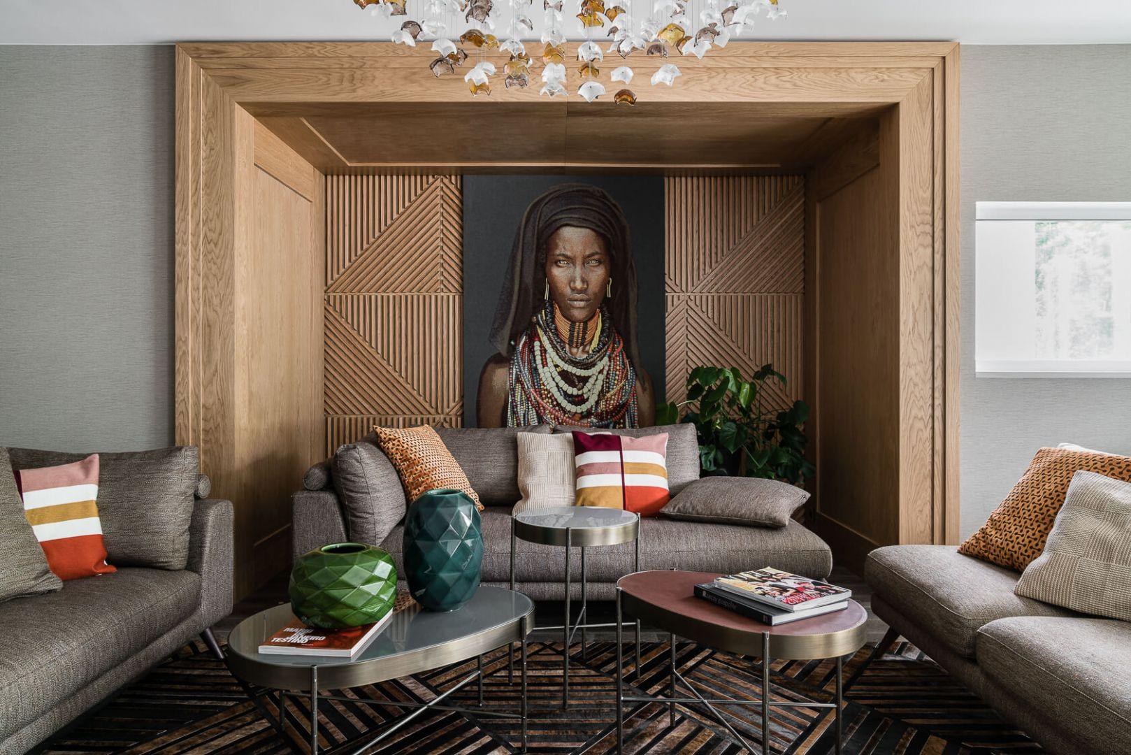 Ścianę za kanapą zdobi obraz w drewnianej instalacji. Projekt Magma. Fot. Fotomohito